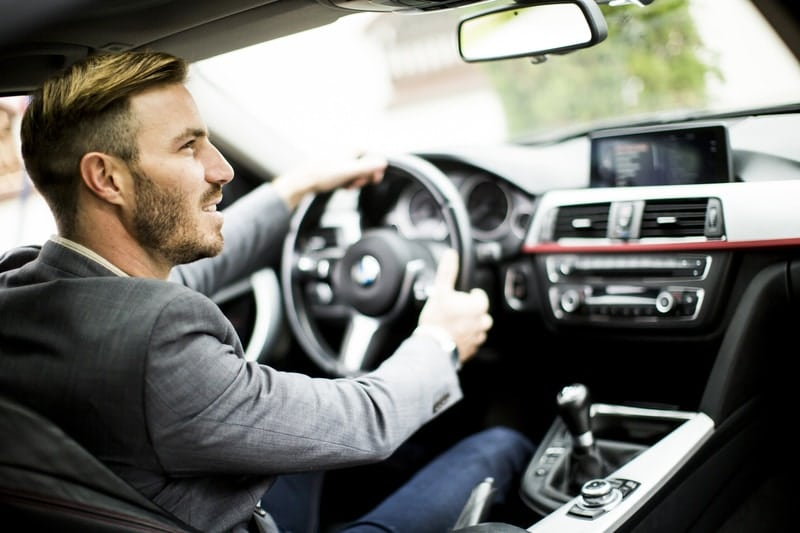 A young, attractive male that is driving a car.