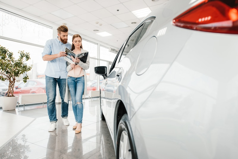 View of a new, white car at a dealership. The camera is angled right at the back left-corner of the car looking towards the front. From this view, you can see a young adult couple reading through a dealership magazine as they walk by the car.