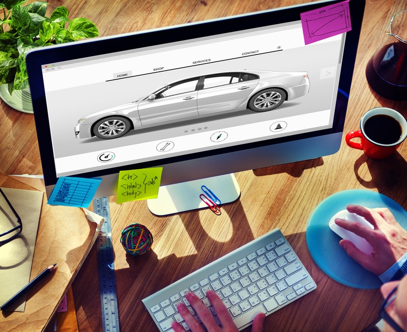 A view of a computer screen surrounded by different notes with writing on them. There is an image of a car on the screen and you can see a person's hands at the keyboard and mouse buying cars online.
