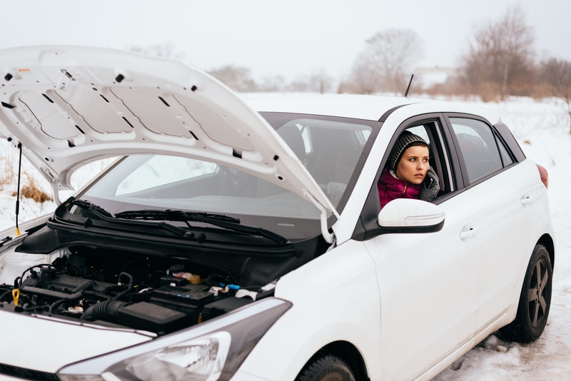 A woman on a cell phone sitting in a white car that is stuck on the side of the road with a dead battery. The front hood is up on the car.