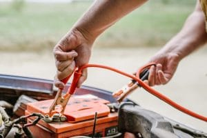 A close-up view of a person putting jumper cables on their car battery to get it charged.