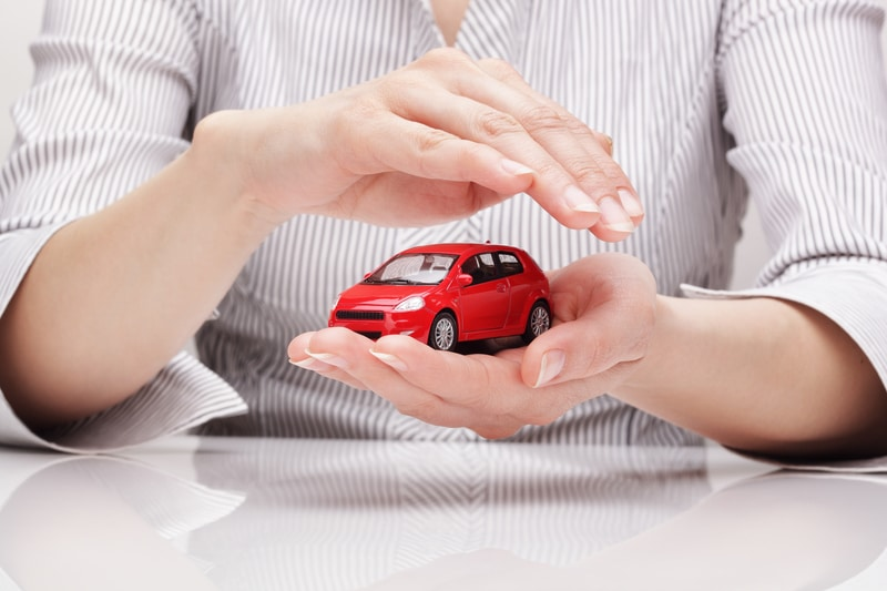 A close-up view of a red car in a person's hands. The person is cradling that car with one hand and covering it with the other to signify car protection