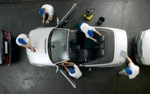 An overhead view of a white convertible car that is being professionally cleaned inside and out at an auto shop.