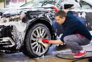 A driver cleaning his black car by hand.