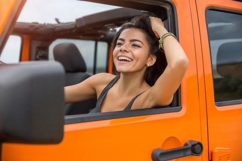 A happy, smiling young brunette woman that is combing her hand through her hair as she drives in her orange car.
