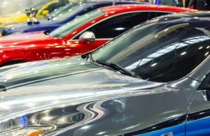 A view of several car hoods that are cars of all different colors. The colors are deeper blue, yellow, silver and red.