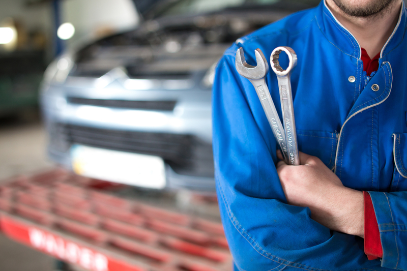 Image of the front of a car service professional in front of a car.