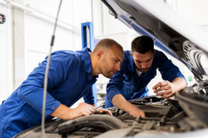 Two professionals working on a car engine in a car shop together.