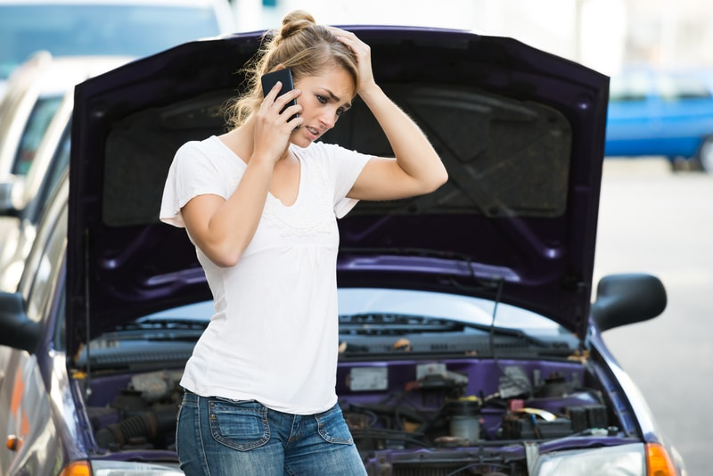 Blonde young adult woman that is on the phone standing in front of her car that has broken down.