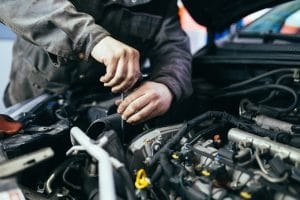 Close-up view of a a car professional working on the engine of a car.