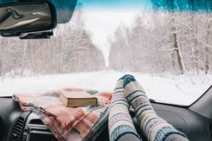 The inside view of a person's feet up on the dash with winter socks on. There is a winter blanket and a book inside the car as the view outside is snowy with snowflakes falling.