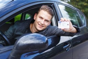 A young teen boy with braces that is hanging out of the driver's window holding a new driver's license.