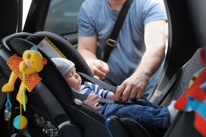 A father is fastening his newborn son into the car as the baby is in an infant safety car seat.