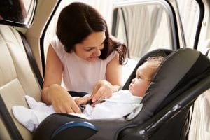 A woman is fastening her small baby into a car seat before driving her car.