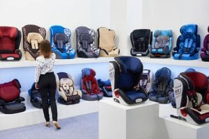 A woman that is looking at various car seats in a store. There is one row on a bottom shelf of car seats and a row above that.