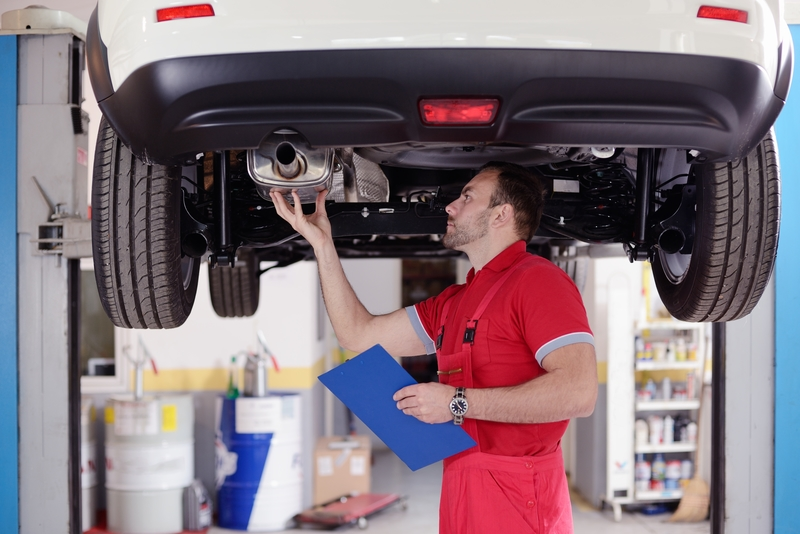 Man doing a car inspection at a professional body shop.