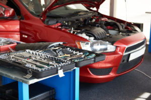 An image of a car with the front hood up and a bunch of car tools in a body shop.