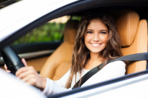 A brunette woman in a car smiling out the window at the camera.