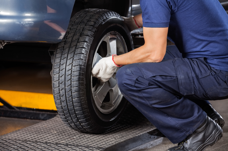 View of a technician adjusting a car tire in a professional shop.