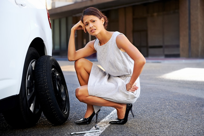 A businesswoman in a work dress that has gotten a flat tire on her car. She is outside the car with the hubcap off and looking as if she is frustrated and doesn't know what to do.