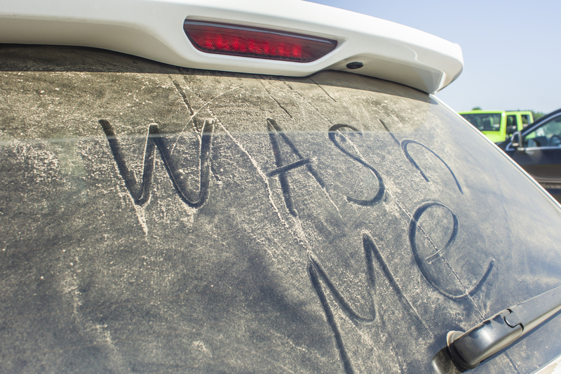 "Back windshield of a car that says ""wash me""."