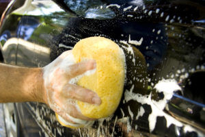 Close-up view of a person washing their car with a big yellow sponge.
