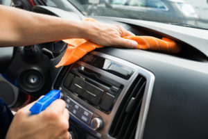 A person that is cleaning the dashboard of their car.