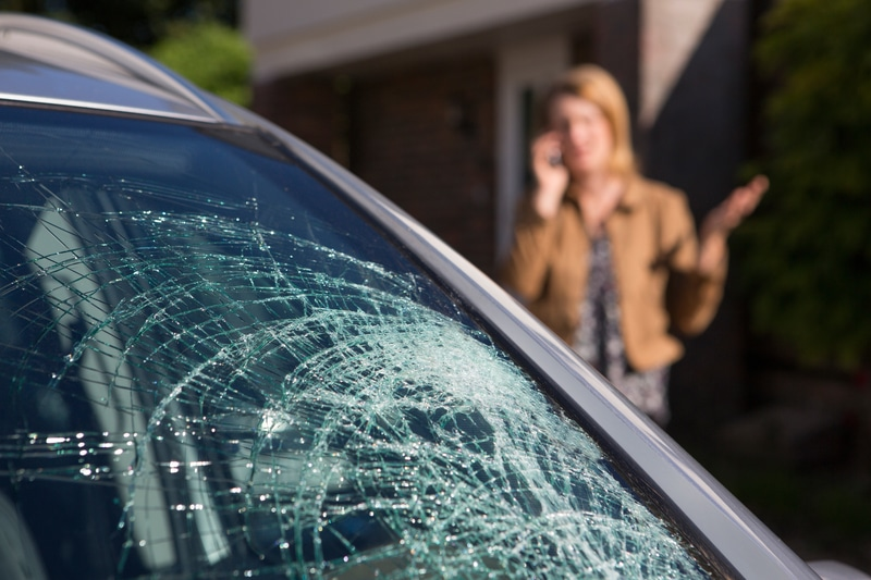 A close-up view of a shattered windshield with a woman in the background talking on the phone to get help for that windshield.