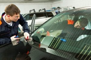 Professionals in a auto shop installing a brand new windshield for a car.
