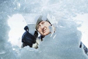 A view from inside the car looking at a man outside the scar that is scraping the ice off of a windshield with a white ice scraper.