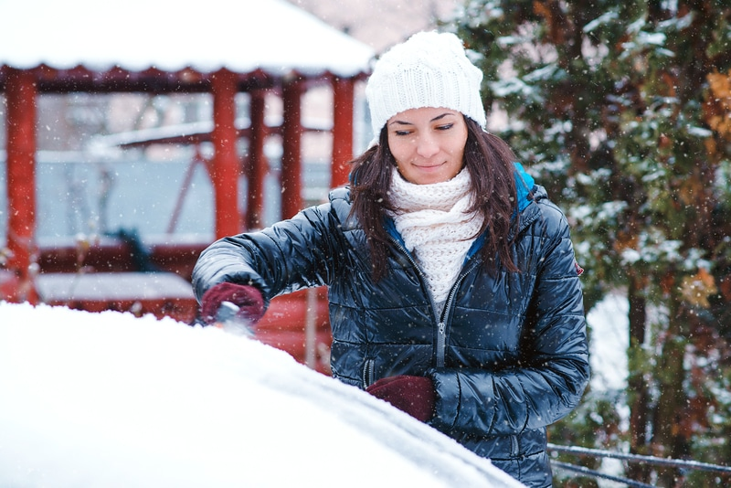 A young adult brunette woman that is scraping the snow and ice from her windshield.
