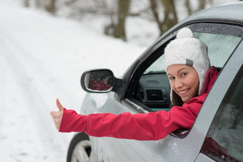 A woman that is about to drive in snow. Her window is rolled down and she is giving the camera a thumbs-up.