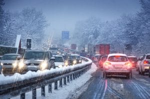 A view of a freeway during the winter packed with driving cars.