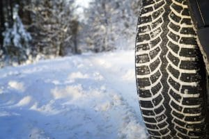 A close-up views of snow tires that have been driving in snow.