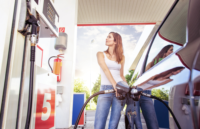 A woman filling her car up with gas.