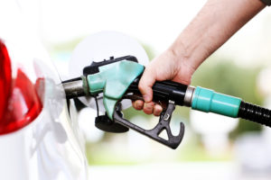A close-up view of a person filling up their car. Only the had is visible with the gasoline pump.