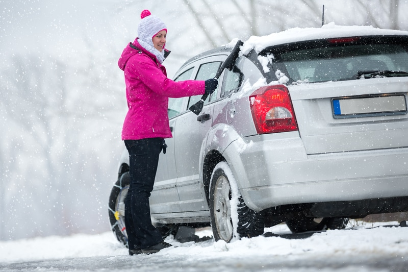 A woman in snow gear with black snow pants and a pink snow coat that is brushing snow off of her car.