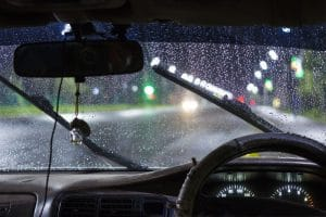 A view of what a driver would see inside a car while it is raining outside and the window wipers are going back and forth.