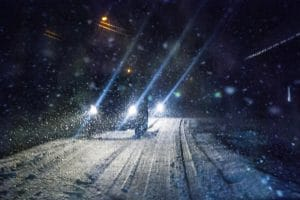 Various cars that are driving towards the camera with headlights on in the snow.