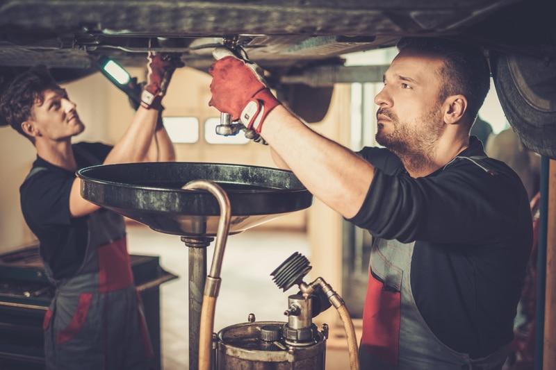 Two mechanics working underneath a car.
