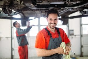 Car professionals that are working underneath a car. One of them is smiling at the camera and cleaning a dipstick.