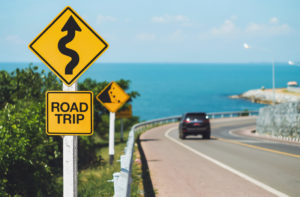 "Sign that says ""road trip"" with a car in the background driving on a winding road."