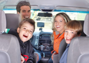 Family in a car before a trip all looking at the camera and smiling.