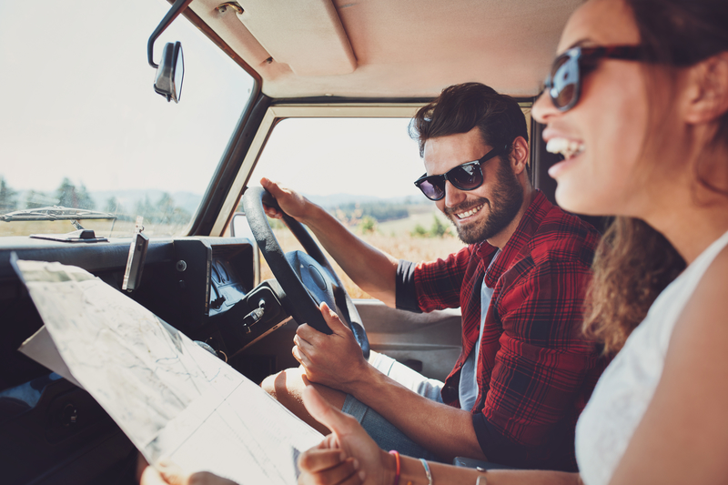 Young man and woman with a map going on a road trip.