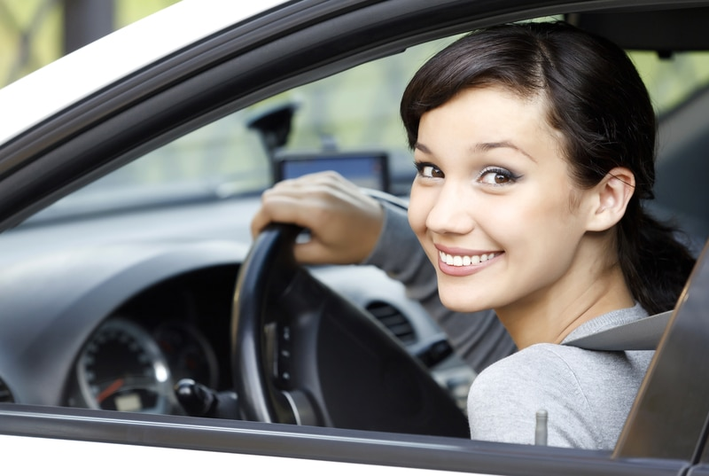 A beautiful, brunette woman that is sitting in a car and smiling out of her window at the camera.