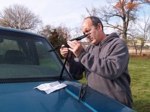 A man that is putting on new windshield wiper blades.
