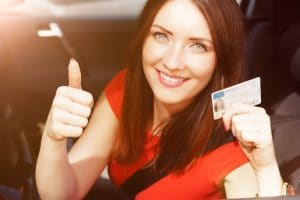 A beautiful brunette woman that is giving the camera a thumbs-up and holding her new license in her other hand.