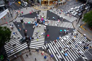 A very large intersection in a huge city. There are 6 different crosswalks in the intersection with crowds of people walking as traffic waits for them.