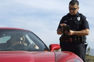 A red sports car that has been pulled over for a speeding ticket. An officer is processing a traffic ticket next to the driver's side of the car.