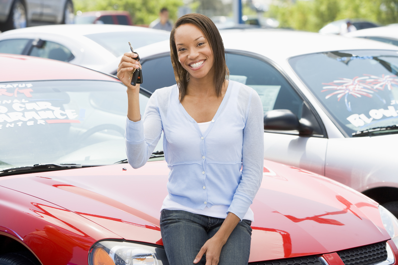 Woman that is sitting on a used red car and holding up keys.
